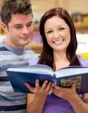 Couples lumineux des étudiants affichant un livre image libre de droits