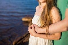 Couples méconnaissables dans l'amour étreignant sur le bord de la mer les mains sont plan rapproché Images libres de droits