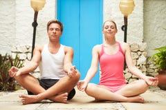 Couples méditant dehors à la station thermale de santé Image stock