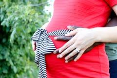 Couples mélangés enceintes tenant le ventre de wifes Photos stock