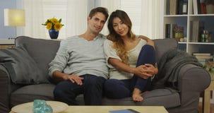 Couples mélangés japonais se reposant sur le sourire de divan images stock