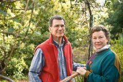 Couples mûrs à leur porte de jardin Photos stock