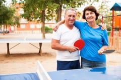 Couples mûrs étreignant près du ping-pong photos stock