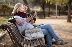 Couples mûrs de sourire échangeant des numéros de téléphone Photos libres de droits