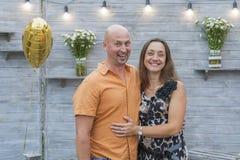 Couples mûrs drôles se tenant sur le fond gris Position d'une cinquantaine d'années de couples sur le fond gris Couples se tenant photo stock