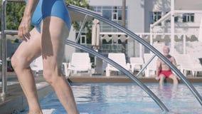 Couples mûrs heureux détendant à la piscine dans le complexe d'hôtel ensemble La femme supérieure attirante prenant un bain de so banque de vidéos