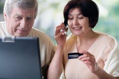 Couples mûrs heureux sur l'ordinateur portatif, faisant des emplettes dans le système d'Internet Images stock
