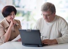 Couples mûrs heureux travaillant sur l'ordinateur portatif Photos libres de droits