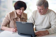 Couples mûrs heureux travaillant sur l'ordinateur portatif Photo stock