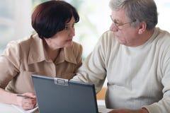 Couples mûrs heureux travaillant sur l'ordinateur portatif Image stock