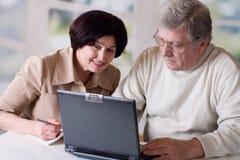 Couples mûrs heureux travaillant sur l'ordinateur portatif Photographie stock