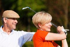 Couples mûrs jouant au golf Photos libres de droits