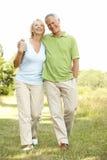 Couples mûrs marchant dans la campagne Image stock