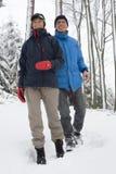 Couples mûrs marchant dans la neige Photo libre de droits