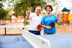 Couples mûrs montrant la victoire près du ping-pong images libres de droits