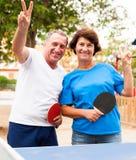 Couples mûrs montrant la victoire près du ping-pong photo stock