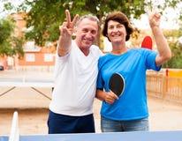 Couples mûrs montrant la victoire près du ping-pong images stock