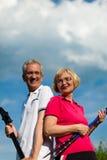 Couples mûrs ou aînés heureux faisant la marche de Nordic Image libre de droits