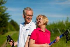 Couples mûrs ou aînés heureux faisant la marche de Nordic Photo stock