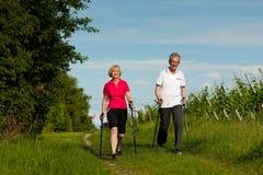 Couples mûrs ou aînés heureux faisant la marche de Nordic Photo libre de droits