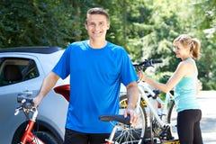 Couples mûrs prenant des vélos de montagne de support sur la voiture Photo libre de droits