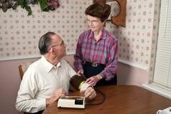 Couples mûrs prenant la tension artérielle photographie stock