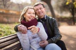 Couples mûrs sur un banc se dirigeant en avant Photographie stock