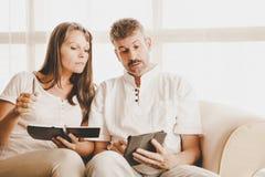 Couples mûrs sur un divan avec le comprimé image libre de droits