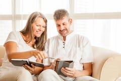Couples mûrs sur un divan avec le comprimé images stock