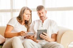 Couples mûrs sur un divan avec le comprimé images libres de droits