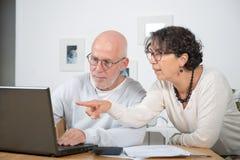 Couples mûrs utilisant l'ordinateur portatif Photo libre de droits