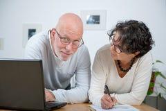 Couples mûrs utilisant l'ordinateur portatif Image stock