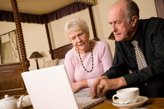Couples mûrs utilisant l'ordinateur portatif Photo stock