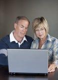Couples mûrs utilisant l'ordinateur portatif Image libre de droits