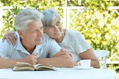 Couples mûrs à une table avec un livre Image libre de droits