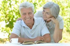 Couples mûrs à une table avec un livre Photo stock
