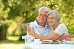 Couples mûrs à une table avec un livre Photo libre de droits