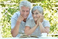 Couples mûrs à une table avec un livre Images stock
