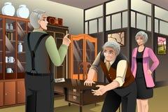 Couples mûrs achetant les meubles antiques Image stock