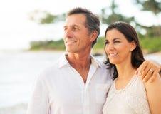 Couples mûrs appréciant le coucher du soleil sur la plage Images libres de droits
