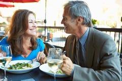Couples mûrs appréciant le repas au restaurant extérieur Photo stock