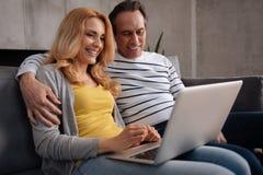 Couples mûrs avec plaisir appréciant le nouvel instrument électronique à la maison Image stock