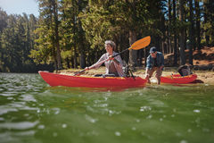 Couples mûrs ayant l'amusement kayaking dans le lac Image stock
