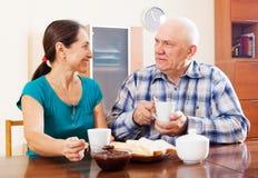 Couples mûrs ayant le thé avec la confiture Image libre de droits