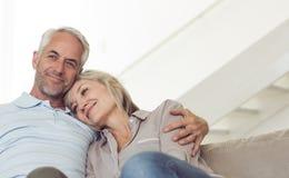 Couples mûrs décontractés se reposant sur le sofa Images stock