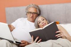 Couples mûrs détendant dans la lecture de lit Image libre de droits