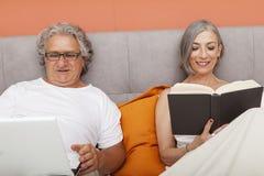 Couples mûrs détendant dans la lecture de lit Photo libre de droits