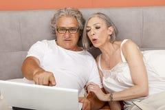 Couples mûrs détendant dans la lecture de lit Images stock