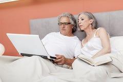 Couples mûrs détendant dans la lecture de lit Photo stock