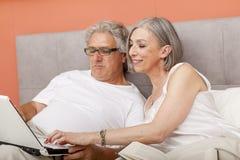 Couples mûrs détendant dans la lecture de lit Photographie stock libre de droits